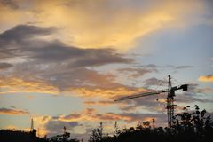 Sunset over the construction site. ,blue sky and clouds, Cranes on the ground Royalty Free Stock Photography