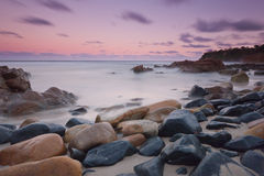 Sunset over Coolum Beach, Queensland. Smooth and rough boulders on the beach at Coolum, Queensland at sunset Stock Image