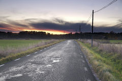 Sunset over country road Royalty Free Stock Images