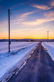 Sunset over a country road through snow covered fields in rural Stock Image