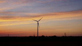 Sunset over the countryside with a wind generator. View from the window of a traveling car. POV video stock video footage