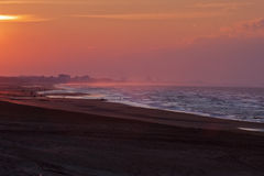 Sunset over Coxyde beach. With  Dunkirk in a foggy background Stock Image
