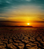 Sunset over cracked earth Royalty Free Stock Photography