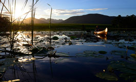 Sunset over dam with canoe in background, Garden Route, South Africa Stock Photo