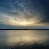 Sunset over dark water Stock Photos