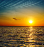 Sunset over dark water Royalty Free Stock Photo