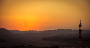 Sunset over desert with muslim mosque in the Stock Photo