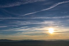 Sunset over distant mountains, with blue sky full of white clouds and vapor trails Royalty Free Stock Photography
