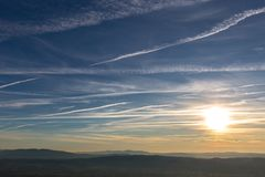 Sunset over distant mountains, with blue sky full of white clouds and vapor trails Stock Photos