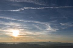Sunset over distant mountains, with blue sky full of white clouds and vapor trails Stock Images