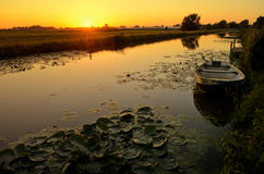 Sunset over a ditch with a boat and waterlily Royalty Free Stock Image