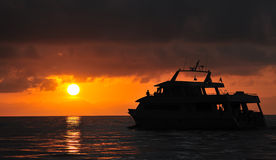 Sunset over dive boat. Orange sunset over sea with silhouetted dive boat in foreground royalty free stock image