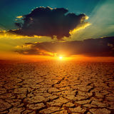 Sunset over drought earth Royalty Free Stock Photo