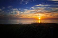 Sunset over dunes on coast Stock Image