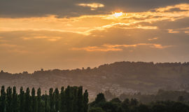Sunset over an English Rural Scene. The sun, setting through clouds, over a typical English hillside, with the shape of a church visible on the top of the hill Royalty Free Stock Photography