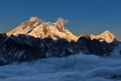 Sunset over Everest summit, view from Renjo La. Sunset over Everest summit, view from Renjo La pass. Amazing view of mountain valley covered with curly clouds royalty free stock photo