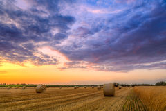 Sunset over farm field with hay bales Stock Photos