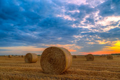 Sunset over farm field with hay bales Stock Images