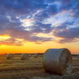 Sunset over farm field with hay bales Royalty Free Stock Photography