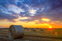 Sunset over farm field with hay bales Stock Image
