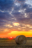Sunset over farm field with hay bales Royalty Free Stock Photos