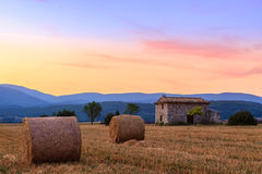 Sunset over farm field with hay bales near Sault Stock Images