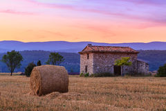 Sunset over farm field with hay bales near Sault royalty free stock photo