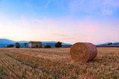 Sunset over farm field with hay bales near Sault Royalty Free Stock Photos