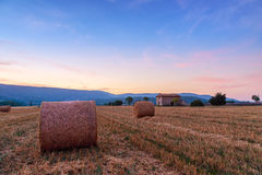 Sunset over farm field with hay bales near Sault Stock Image