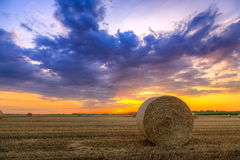 Sunset over farm field with hay bales Royalty Free Stock Images