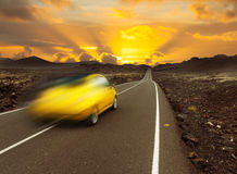 Sunset over fast car and road. Yellow sunset over fast car and  asphalt road, Canary island Lanzarote Royalty Free Stock Photography