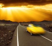 Sunset over fast car and road. Yellow sunset over fast car and  asphalt road, Canary island Lanzarote Stock Photos