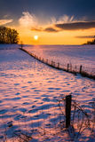 Sunset over a fence in a snow covered farm field in rural Carrol Royalty Free Stock Image