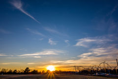 Sunset over field and amusement park indistance Stock Images