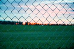 Sunset over field through fence Stock Images