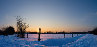 Sunset over a field in snow Royalty Free Stock Photos