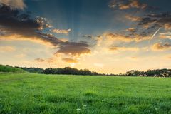 Sunset over the fields. With sunbeams and clouds in the blue sky royalty free stock image