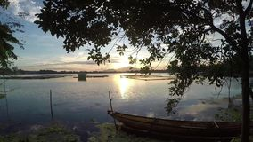 Sunset over floating fisher`s wooden boat anchored at the bay of the lake. Tracking shot, silhouettes stock footage