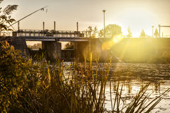 Sunset over floodgate on river Stock Image