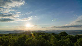 Sunset over forest landscape time lapse. Clouds and trees moving in wind. 4K UHD stock footage