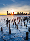 Sunset over Frozen Hudson River and Jersey City. Wood pilings from New York old pier sticking out through the ice on Hudson River at sunset with Jersey City Stock Image