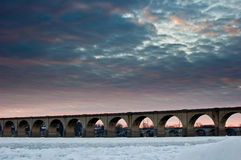 Sunset over Frozen River. An image of beautiful bridge on frozen river during sunset Stock Images