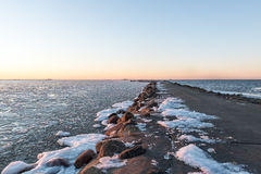 Sunset over frozen sea Stock Images