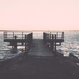 Sunset over frozen sea with old metal bridge - vintage retro eff Stock Photo