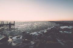 Sunset over frozen sea with old metal bridge - vintage retro eff Royalty Free Stock Photos