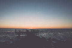 Sunset over frozen sea with old metal bridge - vintage retro eff Stock Image