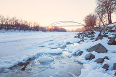 Sunset over frozen Tisza river. With pedestrian bridge in the background Royalty Free Stock Photos