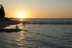 Sunset over Geographe Bay with ocean bathes in foreground. Busselton, Australia has the longest wooden jetty/pier in the Southern Hemisphere stretching almost 2 royalty free stock images