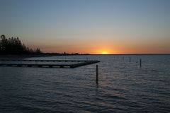 Sunset over Geographe Bay with ocean bathes in foreground. Busselton, Australia has the longest wooden jetty/pier in the Southern Hemisphere stretching almost 2 royalty free stock photo