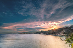 Sunset over Giardini Naxos - Sicily. Sunset over the sea in front of Giardini Naxos, with Etna Volcano in the background, seen from the road to Taormina Royalty Free Stock Photography